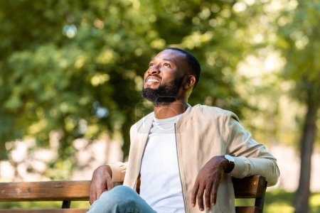 handsome smiling african american man sitting on wooden bench in park and looking up