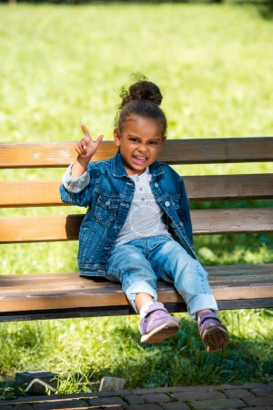 grimacing african american kid gesturing and sitting on wooden bench