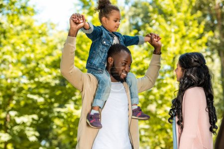 Photo for Smiling african american father holding daughter on shoulders in park - Royalty Free Image