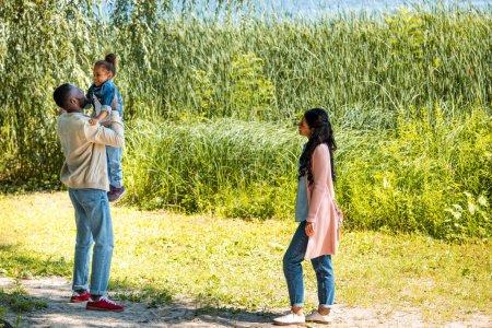 Photo pour Père afro-américain tenant fille dans le parc près de la rivière - image libre de droit
