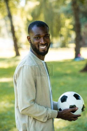 smiling handsome african american man standing with football ball in park and looking at camera