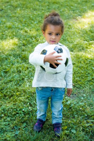 adorable african american kid holding football ball and looking away in park