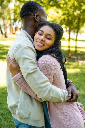 side view of african american couple hugging in park