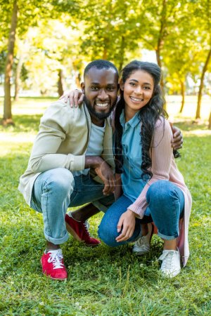 african american couple hugging, squatting and looking at camera in park
