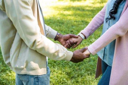 Foto de Recortar imagen de pareja afroamericana mantiene las manos en el Parque - Imagen libre de derechos