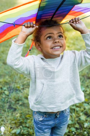 smiling adorable african american kid holding rainbow kite above head in park