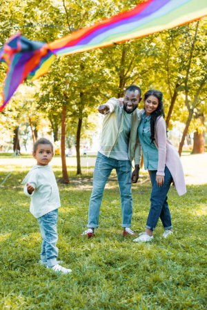 african american father pointing on flying kite to daughter in park