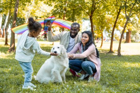 african american parents and daughter with dog and kite in park