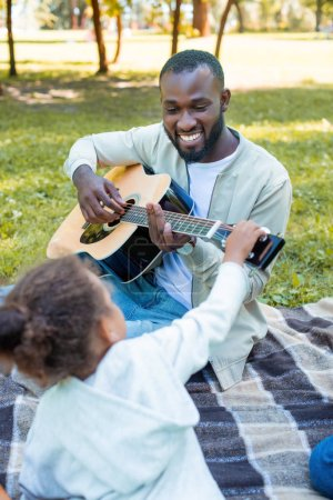 african american daughter touching guitar while her father playing in park