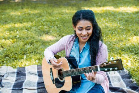 attractive african american guitarist playing acoustic guitar in park