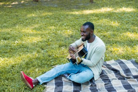 Photo for Handsome african american guitarist playing acoustic guitar in park - Royalty Free Image