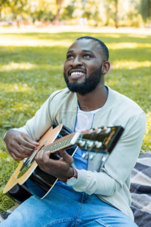 happy handsome african american man playing acoustic guitar in park and looking up