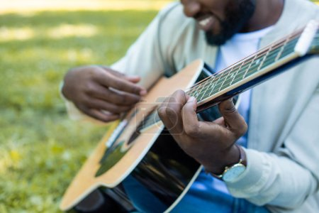 cropped image of african american man playing acoustic guitar in park