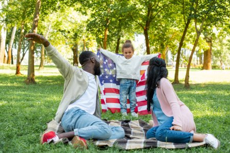 african american daughter pretending flying with american flag in park