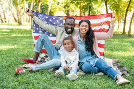 Photo for Smiling african american parents and daughter holding american flag at picnic in park - Royalty Free Image
