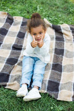 Photo for Adorable african american kid sitting on blanket and showing thumbs up in park - Royalty Free Image