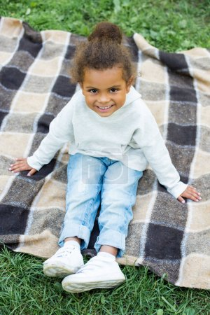 Photo for Smiling adorable african american kid sitting on blanket in park - Royalty Free Image