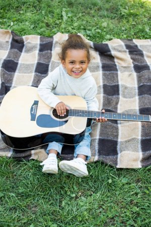 Photo for High angle view of smiling adorable african american kid holding acoustic guitar in park - Royalty Free Image