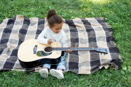Photo for High angle view of adorable african american kid playing acoustic guitar in park - Royalty Free Image