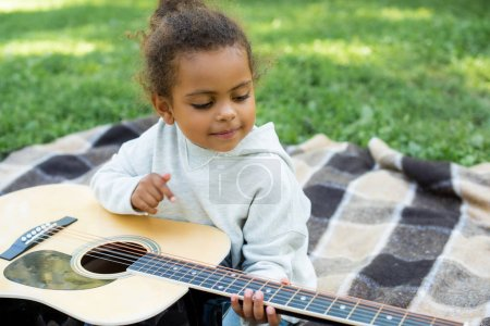 Photo for Adorable african american kid playing acoustic guitar in park - Royalty Free Image