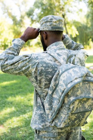 back view of african american soldier in military uniform and bag wearing cap in park