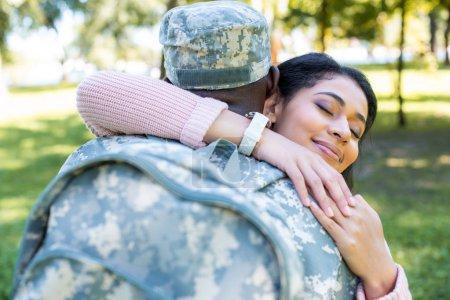 Photo pour Soldat afro-américain militaire uniforme copine de heureux hugging dans le parc - image libre de droit