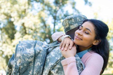 Foto de Soldado americano africano en novia abrazando uniforme militar en el Parque - Imagen libre de derechos