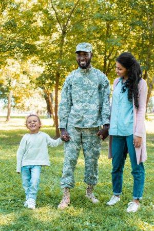 Photo pour Joyeux soldat afro-américain en uniforme militaire, main dans la main avec la fille et la femme dans le parc - image libre de droit