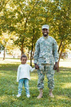 Photo pour Sourire un soldat afro-américain en uniforme militaire et sa fille main dans la main dans le parc - image libre de droit