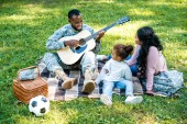 smiling african american soldier in military uniform playing guitar for family in park