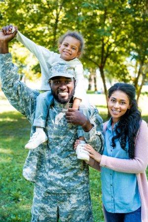 Photo pour Sourire un soldat afro-américain vêtus d'uniformes militaires détenant la fille sur les épaules dans le parc - image libre de droit
