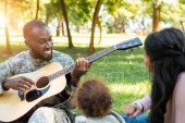 happy african american soldier in military uniform playing guitar for family in park
