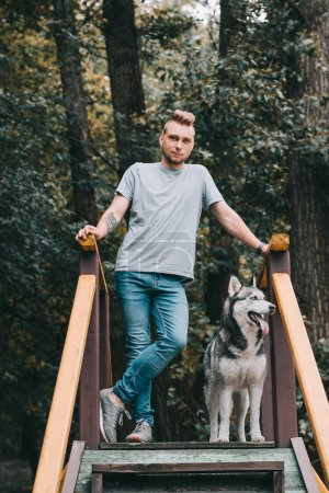 young man posing on stairs with husky dog