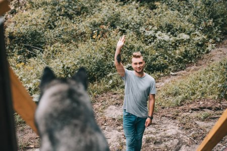 selective focus of young man with siberian husky dog in park