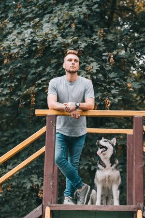 handsome man standing on stairs with husky dog