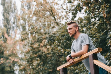 handsome pensive man leaning on railings in park