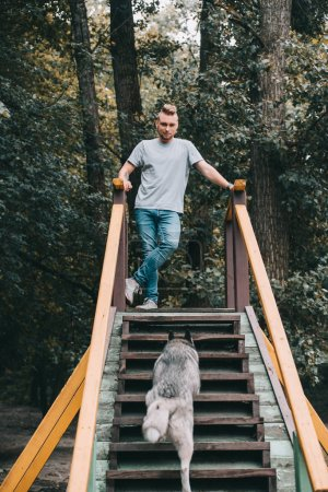 young man with siberian husky dog on stairs in park