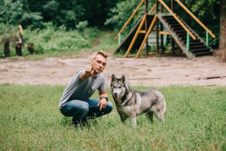 young man showing something to husky dog in park