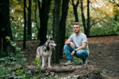 handsome young man walking with siberian husky dog in forest