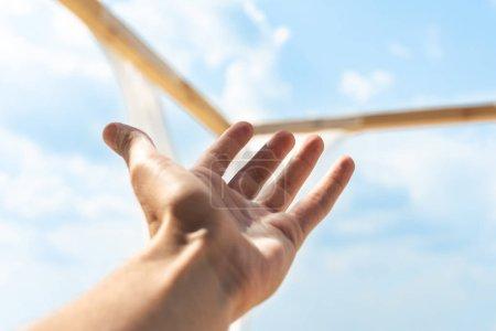 Foto de Vista parcial de la mano masculina y azul cielo nublado sobre fondo - Imagen libre de derechos