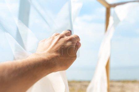 Foto de Vista parcial del hombre que sostiene el cordón de la cortina blanca con azul cielo nublado sobre fondo - Imagen libre de derechos