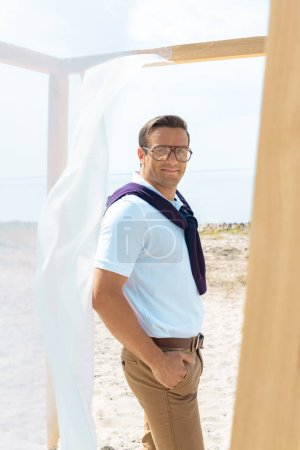 Foto de Hombre guapo en anteojos de pie junto a la decoración con cordón de la cortina blanca en la playa - Imagen libre de derechos
