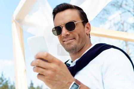 Foto de Retrato de hombre guapo en gafas de sol con smartphone azul cielo nublado sobre fondo - Imagen libre de derechos