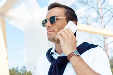 Foto de Retrato de hombre guapo en gafas de sol hablando por teléfono inteligente con azul cielo nublado sobre fondo - Imagen libre de derechos