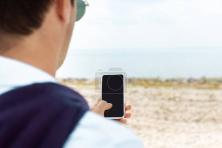 partial view of man using smartphone with blank screen on sandy beach