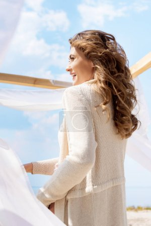 Foto de Vista lateral de mujer feliz mirando lejos con cordón de la cortina blanca sobre fondo - Imagen libre de derechos