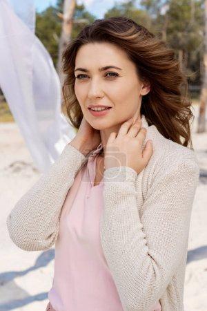 portrait de chère belle femme avec rideau blanc dentelle derrière sur la plage de sable