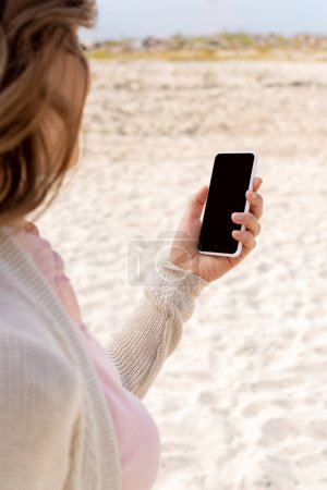 Photo for Partial view of woman using smartphone with blank screen on sandy beach - Royalty Free Image