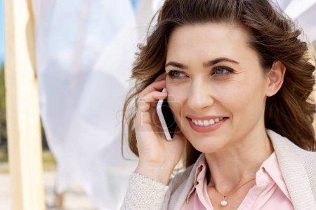 Foto de Retrato de mujer sonriente, hablando por teléfono inteligente con cordón de la cortina blanca sobre fondo - Imagen libre de derechos