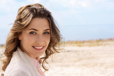 Photo for Portrait of smiling woman looking at camera on sandy beach - Royalty Free Image